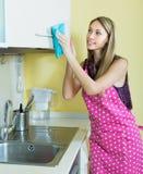 Meisje schoonmakend meubilair in keuken Stock Foto's
