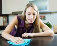 Meisje schoonmakend meubilair in keuken Stock Afbeelding