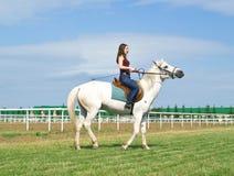 Meisje schrijlings op een paard op een renbaan Stock Afbeelding