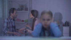 Meisje sluitende oren op regenachtige dag, ouders die in ruimte, conflict ruzie maken stock videobeelden