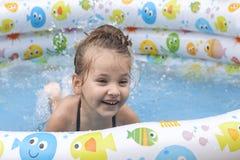 Meisje speel en bespuitend in openlucht water in zwembad stock afbeeldingen