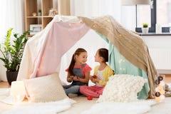 Meisje speeltheekransje in jonge geitjestent thuis royalty-vrije stock foto