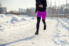 Meisje in sportkleding op een snow-covered van de stadionpasvorm en sport levensstijl in werking die wordt gesteld die Looppas en royalty-vrije stock foto's