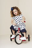 Meisje in spotty kleding op driewieler Stock Fotografie