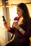 Meisje in stad met smartphone en meeneemkoffie Royalty-vrije Stock Foto's