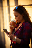 Meisje in stad met smartphone en meeneemkoffie Stock Afbeeldingen