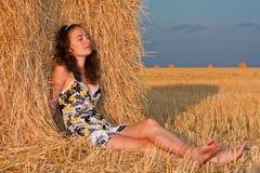 Meisje in stapel van hey Stock Fotografie