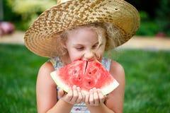 Meisje in strohoed met grote plak van watermeloenzitting op groen gras in de zomerpark stock fotografie