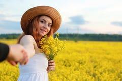 Meisje in strohoed op een gebied van het gele bloemen tot bloei komen Stock Afbeelding