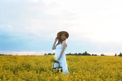 Meisje in strohoed op een gebied van het gele bloemen tot bloei komen Royalty-vrije Stock Foto