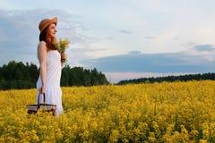 Meisje in strohoed op een gebied van het gele bloemen tot bloei komen Stock Fotografie