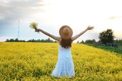 Meisje in strohoed op een gebied van het gele bloemen tot bloei komen Royalty-vrije Stock Afbeeldingen