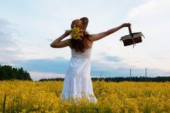 Meisje in strohoed op een gebied van het gele bloemen tot bloei komen Stock Foto's
