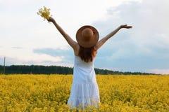 Meisje in strohoed op een gebied van het gele bloemen tot bloei komen Stock Foto