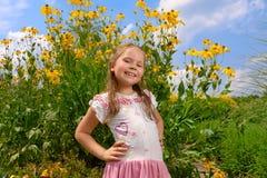 Meisje tegen gele bloemen en de blauwe hemel Royalty-vrije Stock Afbeeldingen