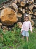 Meisje tegen gestapelde gezaagde houten logboeken stock fotografie