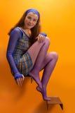 Meisje tegen oranje muur Royalty-vrije Stock Foto's
