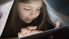 Meisje tien van de gebruiks digitale jaar tablet onder dekking, bij nacht stock video