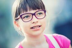 Meisje tiener Pretiener Meisje met glazen Meisje met tandensteunen Jong leuk Kaukasisch blond meisje die tandensteunen en glazen  Stock Afbeeldingen