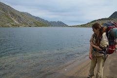 Meisje, toerist, op de kusten van een alpien meer in de bergen Stock Fotografie