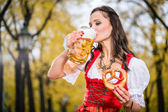 Meisje in traditioneel Beiers Tracht-het drinken bier uit reusachtige mu royalty-vrije stock foto's
