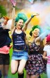 Meisje twee tijdens Holi-festival werpt kleurenverven stock foto