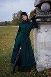 Meisje in uitstekende groene laag in het park Stock Foto's