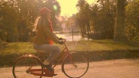 Meisje in uitstekende manier berijdende fiets bij het park stock videobeelden