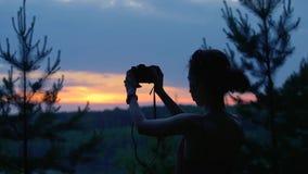 Meisje van achter het fotograferen op het strand SunsetGirl met fotocamera in retro hipsterontwerp maakt een foto van a stock footage