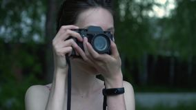 Meisje van achter het fotograferen op het strand SunsetGirl met fotocamera in retro hipsterontwerp maakt een foto van a stock videobeelden