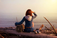 Meisje van de Hipster het jonge toerist in jeans, tennisschoenen met een zakzitting royalty-vrije stock fotografie