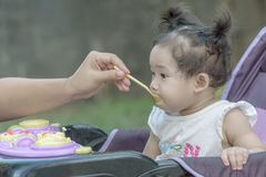 Meisje van de moeder het voedende baby met havermoutpap Stock Fotografie