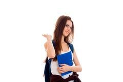 Meisje van de schoonheids het jonge donkerbruine die student met rugzak en omslagen voor notitieboekjes in handen op witte achter Royalty-vrije Stock Fotografie