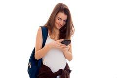 Meisje van de schoonheids het jonge donkerbruine student met rugzak met mobiele die telefoon op witte achtergrond wordt geïsoleer Royalty-vrije Stock Foto