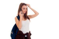 Meisje van de schoonheids het jonge donkerbruine student met rugzak sprekende die telefoon op witte achtergrond wordt geïsoleerd Stock Foto's