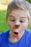 Meisje van een vlinder op haar neus wordt verrast die stock foto