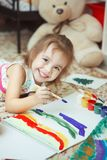 Meisje van goede stemming het schilderen regenboog met borstel Stock Foto