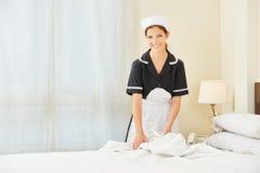 Meisje veranderend linnen voor bed in hotelruimte stock fotografie