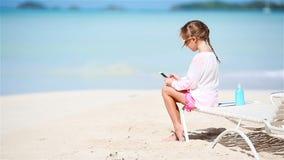 Meisje video maken of de foto met door haar camerazitting op sunbed stock video