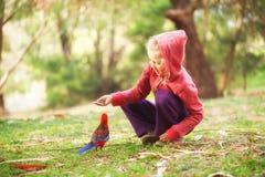 Meisje voedende papegaai Stock Foto's