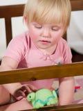Meisje in voederbak het spelen met stuk speelgoed Stock Foto's