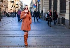 Meisje in volledige lengte die en een lolly in de stad bevinden zich houden Stock Afbeelding