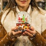 Meisje in warme het glasbal van de laagholding met sparren, huis en kunstmatige sneeuw in een wandelgalerij bij de Kerstmismarkt  stock fotografie