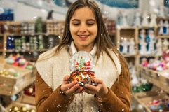 Meisje in warme het glasbal van de laagholding met sparren, huis en kunstmatige sneeuw in een wandelgalerij bij de Kerstmismarkt  stock afbeeldingen
