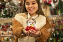 Meisje in warme het glasbal van de laagholding met sparren, huis en kunstmatige sneeuw in een wandelgalerij bij de Kerstmismarkt  stock afbeelding