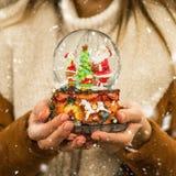 Meisje in warme het glasbal van de laagholding met sparren, huis en kunstmatige sneeuw in een wandelgalerij bij de Kerstmismarkt  stock foto's