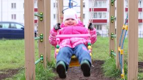 Meisje in warme klerenschommeling op speelplaats en glimlachen stock videobeelden