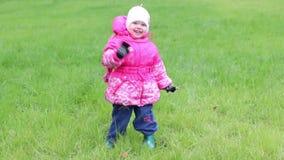 Meisje in warme klerentribunes op gras en golvenhand stock video