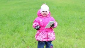 Meisje in warme klerentribunes op gras met witte tablet en glimlachen stock video