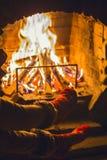 Meisje in warme sokken warme benen dichtbij de open haard Rust, ontspanning dichtbij de open haard in de winter Comfortabele de w stock foto